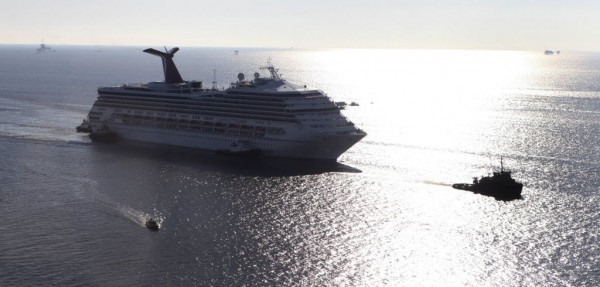 The Carnival Triumph cruise ship is towed towards the port of Mobile, Alabama, February 14, 2013. The 893-foot (272 meter) vessel, notorious for reports of raw sewage from overflowing toilets, has been without propulsion and running on emergency generator power since Sunday, when an engine room fire left it adrift in the Gulf of Mexico.