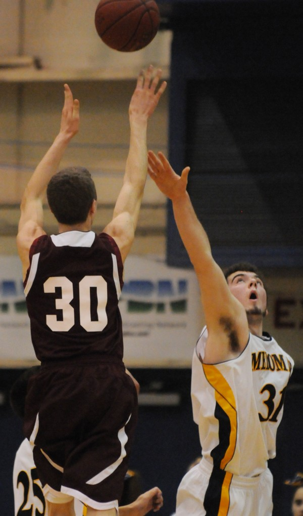 Foxcroft Academy's Hunter Smith shoots over Medomak Valley's Ryan Ripley during first half action on Wednesday at the Bangor Auditorium during Class B tourney action.