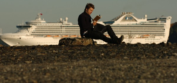 Robert Barth, a tourist from Holland, catches up on his reading on Oct. 25, 2007, during low tide in Bar Harbor as the cruise ship Norwegian Dawn sits at anchor in the harbor.