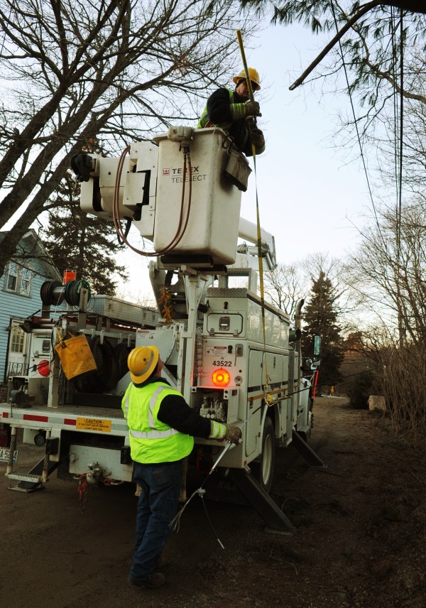 A crew from Bangor Hydro works to restore power along Huston Lane in Eddington on Friday. Nicole Hanson, who lives on Route 9 in Eddington, posted lime green signs drawing attention to downed power lines in hopes of getting swift attention to being without power for over 24 hours. Her power was restored at 5:30 p.m. Friday.
