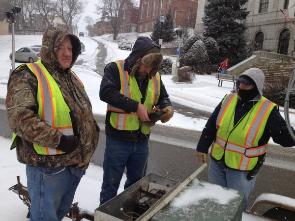 Bangor Public Works employees set up a parking ban sign on Harlow Street in downtown Bangor.