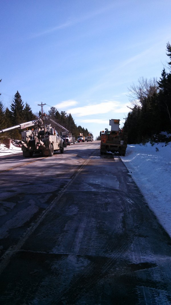 Crews from the Eastern Maine Electric Cooperative work to restore power and reopen a section of Route 1 after two utility poles fell across the roadway at about 5 a.m. Tuesday about eight miles southeast of Calais.