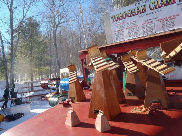 The trophies for the 2013 U.S. National Toboggan Championships at Camden Snow Bowl sit on the roof of an antique truck on Saturday before being claimed by the day's winning teams. Competitors warm up by a fire in the background.