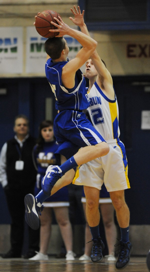 Central Aroostook's Chandler Brewer takes a shot over Washburn's Nicholas Bragg during first half action on Thursday at the Bangor Auditorium during class D tourney action.
