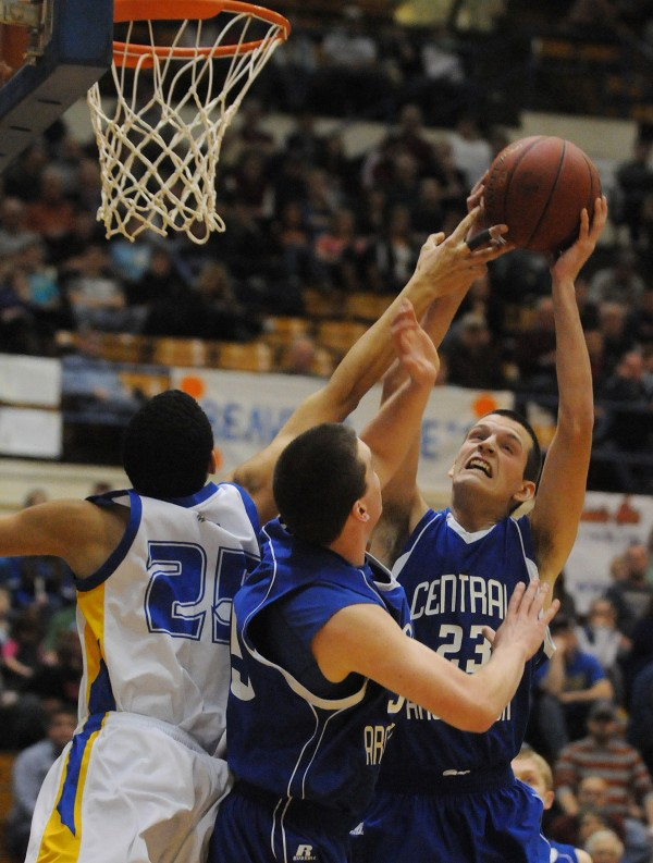 Central Aroostook's Steven Decker takes a shot over Washburn's Cameron Preston, Central Aroostook's Zack McClung is also in on the action (center) during first half action on Thursday at the Bangor Auditorium during class D tourney action.