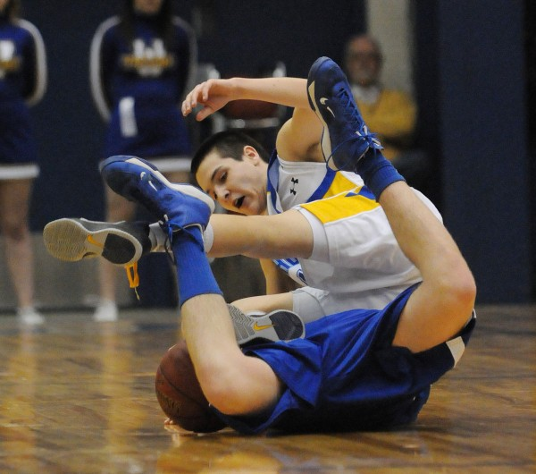 Central Aroostook's Joe Stiles gets tangles with Washburn's Noah Caron while chasing down a loose ball during first half action on Thursday at the Bangor Auditorium during Class D tourney action.
