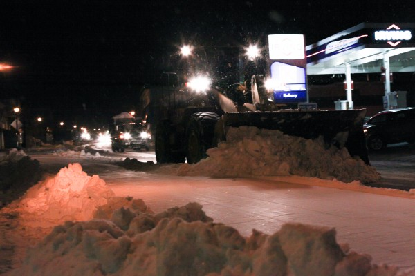 A plow pushes snow along Main Street in Fort Kent on Friday to construct a raceway for mushers and their teams in preparation of the Can-Am Crown starting Saturday. Fort Kent town workers and volunteers constructed the raceway along Main Street.