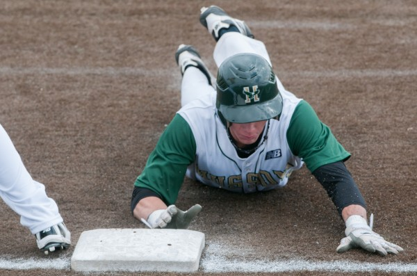 Husson's Benjamin McLain slides back for first base to avoid a tag out  during the first game of a doubleheader against the University of Maine-Presque Isle on Saturday, March 23, 2013.