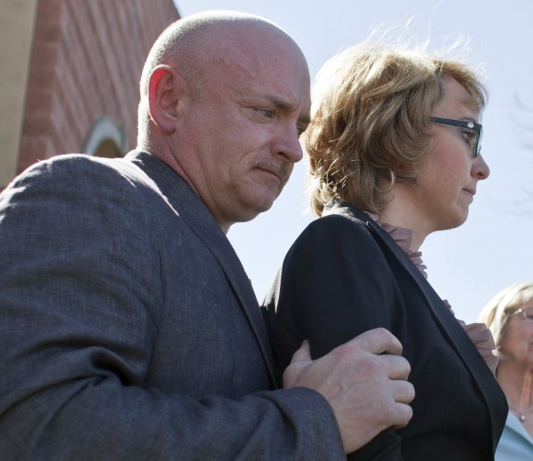 Former congresswoman Gabrielle Giffords and her husband, Mark Kelly, address a new conference for the victims of the January 8, 2011, Tucson shooting, at the Safeway grocery store parking lot where Giffords was shot in Tucson, Arizona, March 6, 2013.