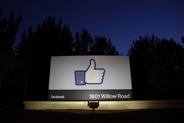 The sun rises behind the entrance sign to Facebook headquarters in Menlo Park, Calif.
