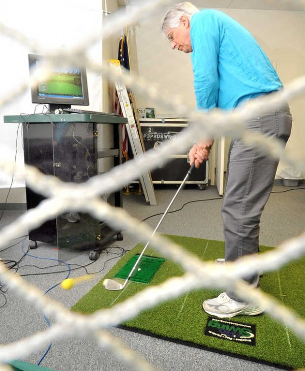 P3 owner and former Maine candidate for governor Les Otten hits a golf ball into a net at his virtual golf manufacturing warehouse in Bethel on Thursday morning.
