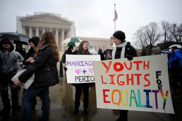 Cassandra Dikson, center, and Megan Eigsti, right, hold signs in support of same-sex marriage in Washington, D.C., on Monday, March 25, 2013. The Supreme Court will hear oral arguments on same-sex marriage on Tuesday.