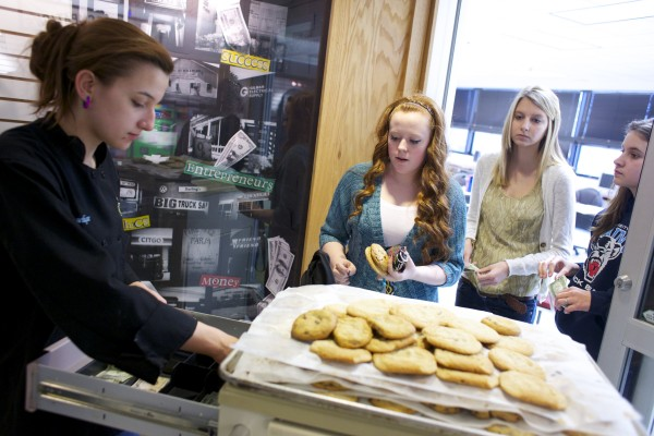 "Angelique Tompkins (from left), a culinary student at United Technologies Center, brings cookies to Hermon High School and Bridge Year students Taylor Smith, Haylie Blackmer and Raven Churchill during their business classes at UTC. The Bridge Year Program enables high school students to earn college credits, at a significant cost savings,€"" during their junior and senior years and summer vacations."