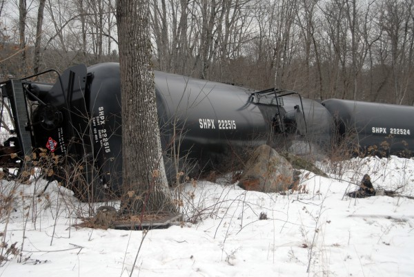 A derailed oil tanker, one of 13, lies on its side near Route 2 and just yards from the Penobscot River in Winn on Thursday, March 7, 2013.