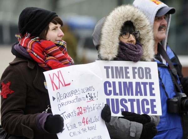 Demonstrators hold signs during a rally in solidarity with the Washington, D.C., protest against the Keystone XL pipeline and for environmental action in Edmonton, on Feb. 17, 2013.