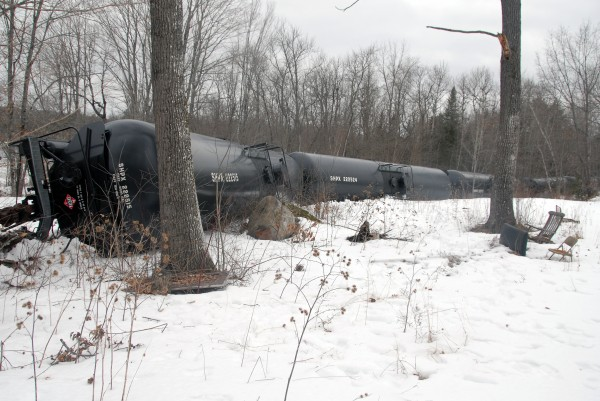 A derailed oil tanker, one of 13, lies on its side near Route 2 and just yards from the Penobscot River in Mattawamkeag on Thursday, March 7, 2013.