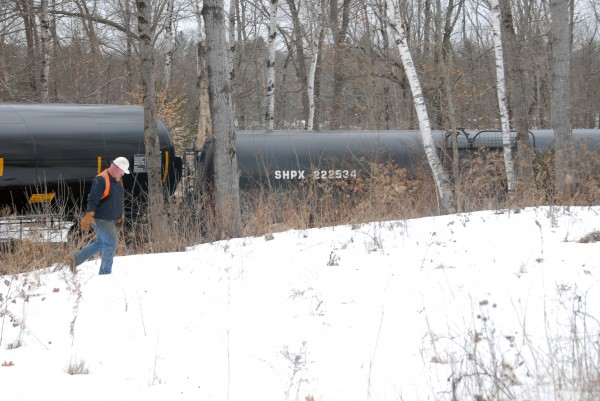 An unidentified worker walks past a derailed oil tanker, one of 13, that lies on its side near Route 2 and just yards from the Penobscot River in Mattawamkeag on Thursday, March 7, 2013.
