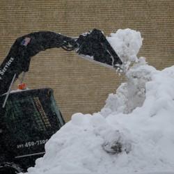 """Workmen clear snow from a private parking lot on Myrtle Street on Sunday, Feb. 24, 2013, in Portland, making way for cars carrying people coming to the Portland Symphony Orchestra's """"A Night at the Movies"""" pops concert."""