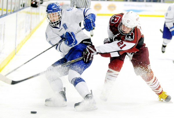 Bryan Hall (left) of Lewiston and Sam Huston of Bangor battle for the puck during the second period during the Eastern Maine Class A final on Tuesday in Lewiston. Lewiston defeated Bangor 5-1.