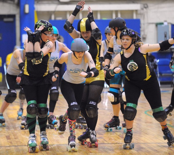 The R.I.P. Tides jammer Byte Size Bandit (center) scores as she breaks through the wall formed by Central Maine Derby players at the Bangor Auditorium Sunday afternoon.