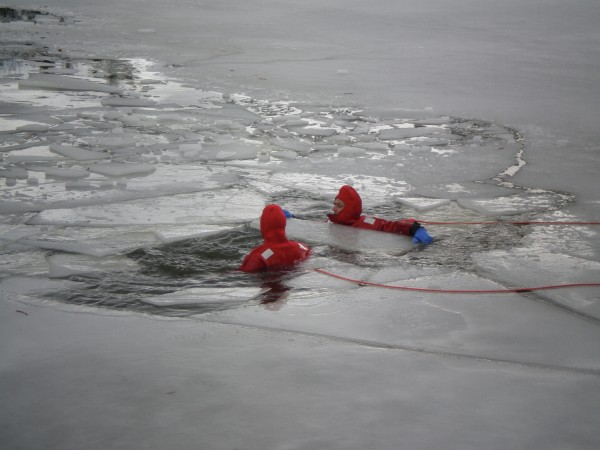 Capt. Mike Clarke and firefighter Mike Drake of the Bath Fire Department wear rescue suits attached by 600-foot tether lines, as well as flotation devices, during ice rescue training Monday on Whiskeag Pond in North Bath.