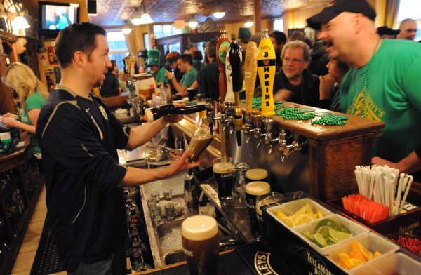 Bartender Chris Rudolph pours beer for patrons of Paddy Murphy's shortly after 6 a.m. Sunday, St. Patrick's Day.