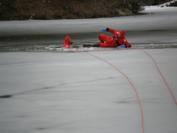 Bath firefighters Mike Drake (left) and Shawn Riley train for a &quotperson through the ice&quot scenario on Whiskeag Pond in North Bath on Monday.