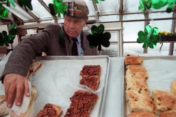Rick Gilbert, surrounded by shamrocks, reaches for a pastry at his farmers market in 2003.