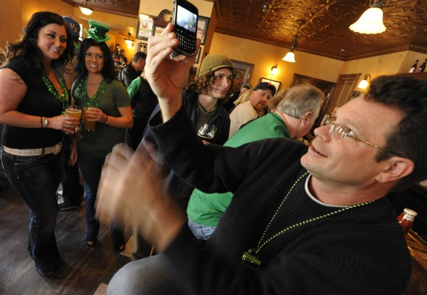 Raynel Dwelley (left) of Brewer and Amaris Coudreau of Orrington enlisted the help of Brian Roth (right) of Orono in taking their picture with one of their cellphones during daytime St. Patrick's Day festivities at Paddy Murphy's in downtown Bangor in 2011.