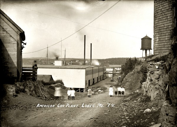 In this circa 1910 photograph, children pose near the American Can Company plant built in Lubec village after its North Lubec factory burned. The first mechanized &quottin&quot can manufacturer in Lubec, it soon erected a much larger building, and those shown here became warehouses. In a few decades the company was turning out 350 million cans a year. Lubec and Eastport canneries employed many children, attracting the attention of well-known documentary photographer and social reformer Lewis Hine. In August 1911 he photographed young workers, many under the age of 12, cutting and packing fish in local canneries.
