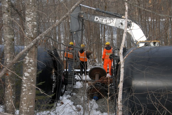 Workers from Pan Am Railways, the Maine Department of Environmental Protection and a contractor continued to work Friday, March 8, 2013, to pump oil from 13 oil tankers that tipped over the day before in Mattawamkeag.