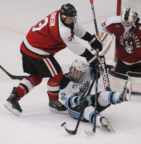 The University of Maine's Stu Higgins (center) scrambles for the puck with Northeastern's Josh Mason in front of Northeastern goalie Chris Rawlings during the second period of the game in Orono on Friday evening, March 1, 2013.