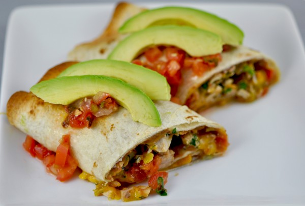Shredded chicken joins mild green chiles, cilantro, tomatoes, green onions, cheese and beans as filling for burritos. Salsa and sliced avocados finish the easy dish.