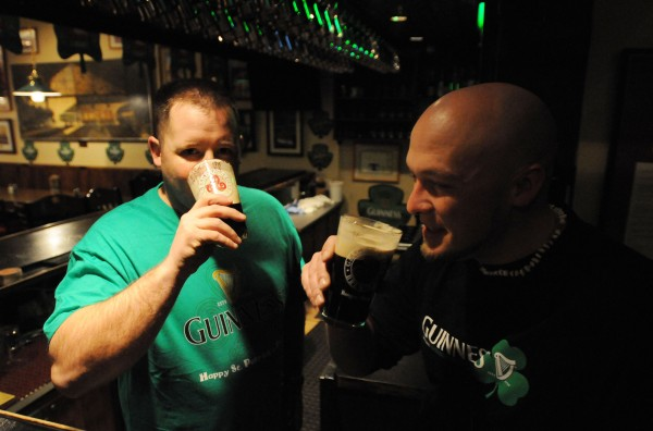 Beer merchandisers Bruce Morneault and AJ Smith sip beer at Geaghan's Pub shortly after 6 a.m. Sunday, St. Patrick's Day. Larry Geaghan chose to open the pub's doors at the regular 7 a.m. time rather than 6 a.m. as allowed by recent changes to state law. Morneault and Smith started at 4 a.m. decorating various pubs and bars that buy liquor from Pine Tree Trading Co., their employer.