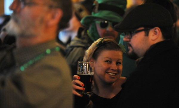 Danielle Dorrie flashes her glass of Guinness beer as she joins a packed bar at Paddy Murphy's early on Sunday, St. Patrick's Day.