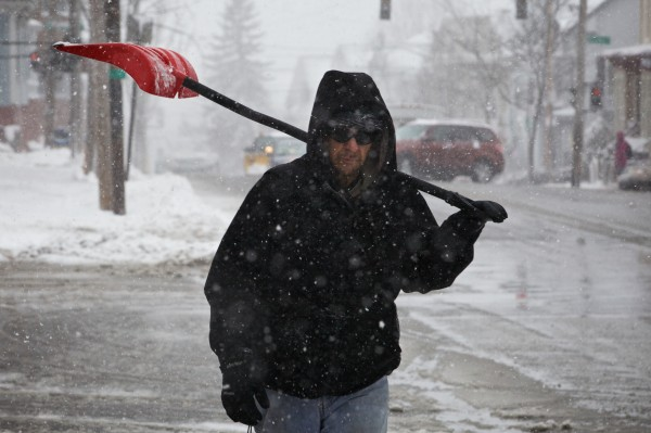 Mark Jackson trudges down Congress Street in Portland on Tuesday, shovel in hand, during the last snowstorm of the winter. Jackson clears snow for a about a dozen clients in the city as a sideline job.