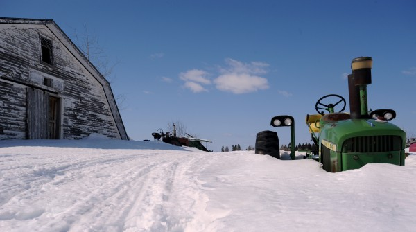 A tractor sits buried in several feet of snow in the yard at the Norris & Brown Farm in Caribou in March 2008. The total snowfall in Caribou that year was the highest since record keeping began in 1939.
