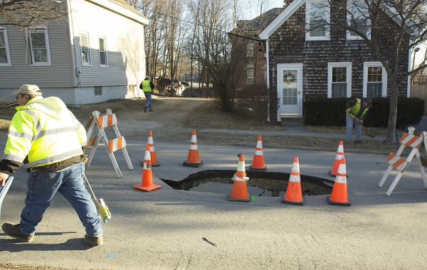 City of Bangor employees fill a sinkhole Monday morning that formed on Lincoln Street over the weekend.