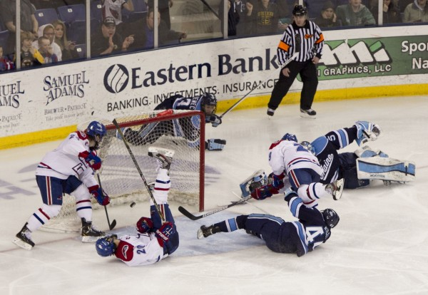 UMass Lowell's Derek Arnold (right) scores the winning goal in overtime against Maine, Friday, March 15, 2013, in Lowell, Mass., during the second game of their Hockey East quarterfinal playoff series. Maine players on the ice are Conor Riley (front), goalie Martin Ouellette and Mark Nemec.