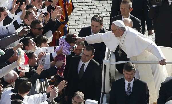 Pope Francis leans out to touch a child's head as he arrives in Saint Peter's Square for his inaugural mass at the Vatican, on Tuesday, March 19, 2013. Pope Francis celebrated his inaugural mass among political and religious leaders from around the world and amid a wave of hope for a renewal of the scandal-plagued Roman Catholic Church.