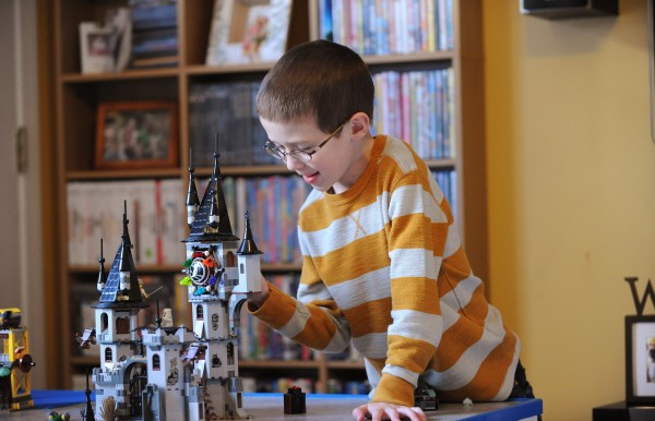 Lucas Rudnicki plays with plastic building toys in the living room of his family's Levant home on Friday. Lucas will donate some of his bone marrow to help his little sister, who suffers from a rare illness, Diamond Blackfan anemia, a disorder that prevents her body from generating red blood cells.