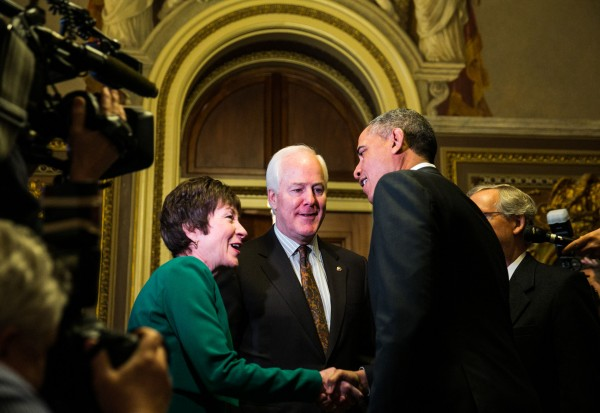 President Barack Obama is greeted by Senators Susan Collins (R-ME) and John Cornyn (R-TX) as he arrives at the U.S. Capitol to meet with Senate Republicans on Capitol Hill in Washington, D.C., Thursday, March 14, 2013.