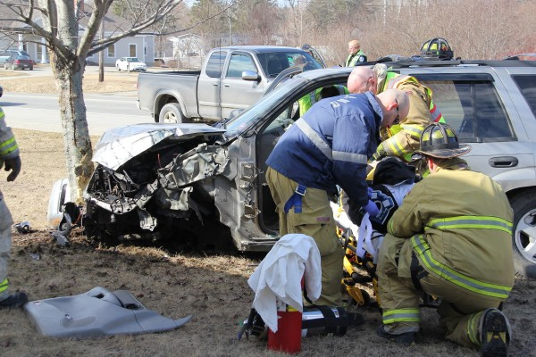 Rescue personnel attend to a man injured in a car crash Thursday morning on Route 1 in Rockland.