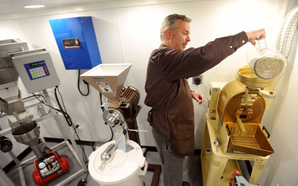 Jeff Savage of Savage and Sons Gourmet Coffee dumps raw coffee beans into the roaster at his home in Bangor in April 2011. Savage started the business in November 2010 and produces three kinds of fresh roasted coffee.