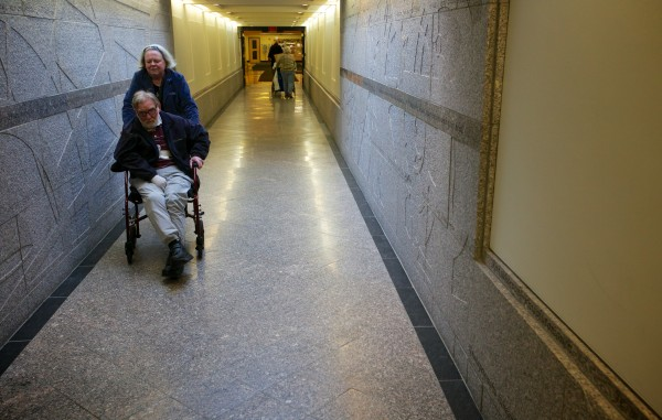 Rep. Ann Peoples, D-Westbrook, pushes her husband Patrick through the underground passage from the Cross Building to the State House Friday in Augusta.