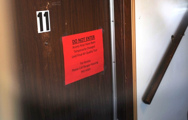 A warning sign is posted on the door of apartment No. 11 at the Autumn West apartment complex at 678 Union Street in Bangor on Monday after tenants were moved out due to poor air quality.