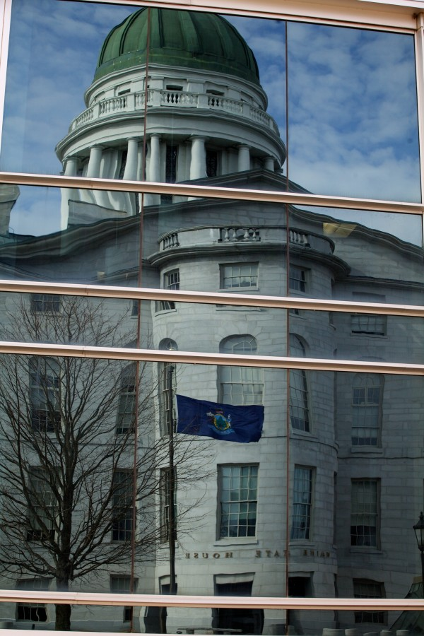 The Maine State House in Augusta is reflected in the windows of the Burton Cross building.