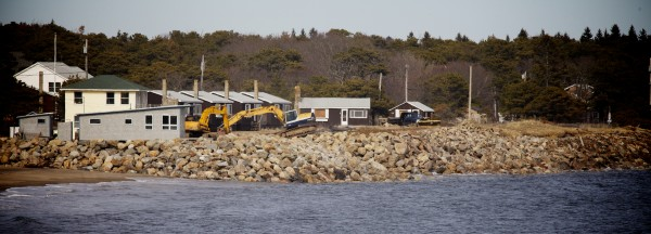 Excavators work to place tons of rock in front of a string of buildings at Popham Beach in Phippsburg Monday.