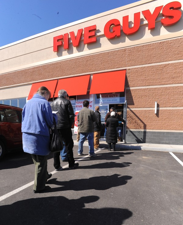 People stand in line waiting to get into the new Five Guys that opened Monday in Bangor.