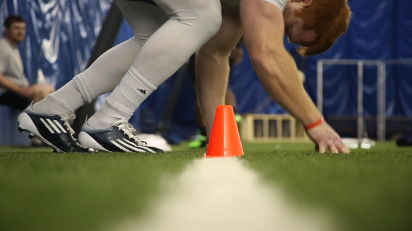 A prospect touches the line during a drill at the University of Maine's NFL pro day workouts on Wednesday, March 20, 2013.